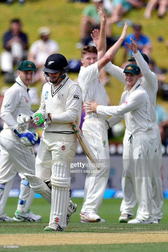 Australia celebrate New Zealand's Henry Nicholls (L) being bowled during day four of the first cricket Test match between New Zealand and Australia at the Basin Reserve in Wellington on February 15, 2016. / AFP / Marty Melville