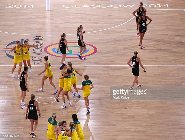 Australia celebrate victory as the New Zealand players leave the court the gold medal netball match between Australia and New Zealand at the SECC...