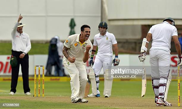 Australia cricketer Mitchell Johnson celebrates after bowling out South Africa's batsman Hashim Amla for a duck during the second test match between...