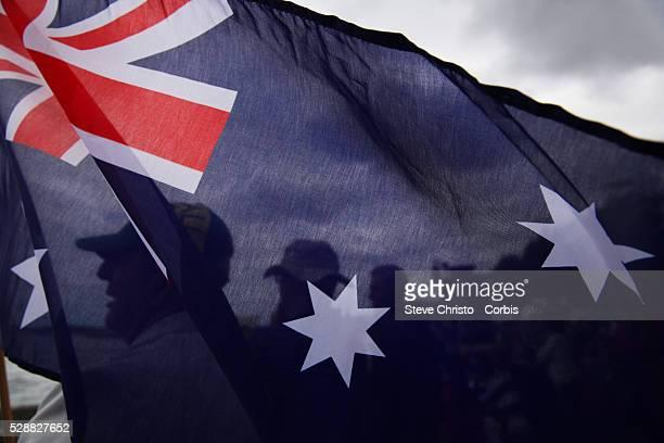 Australia Day celebrations on Sydney Harbour foreshore Spectators wave flags as a procession of boats pass under the Sydney Harbour Bridge Sydney...