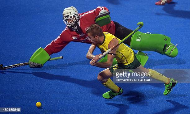 Australia hockey player Jacob Whetton attempts a goal as Pakistan goalkeeper Imran Butt dives to stop the ball during their Hero Hockey Champions...