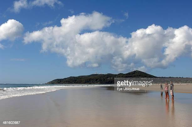 Australia New South Wales Byron Bay Tourists walking along the sandy shoreline beneath blue sky with white cloudscape