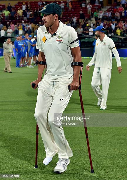 Australia paceman Mitchell Starc walks onto the field with crutches at the end of first daynight cricket Test match at the Adelaide Oval on November...