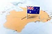 The flag of Australia pinned on the map. Horizontal orientation. Macro photography.