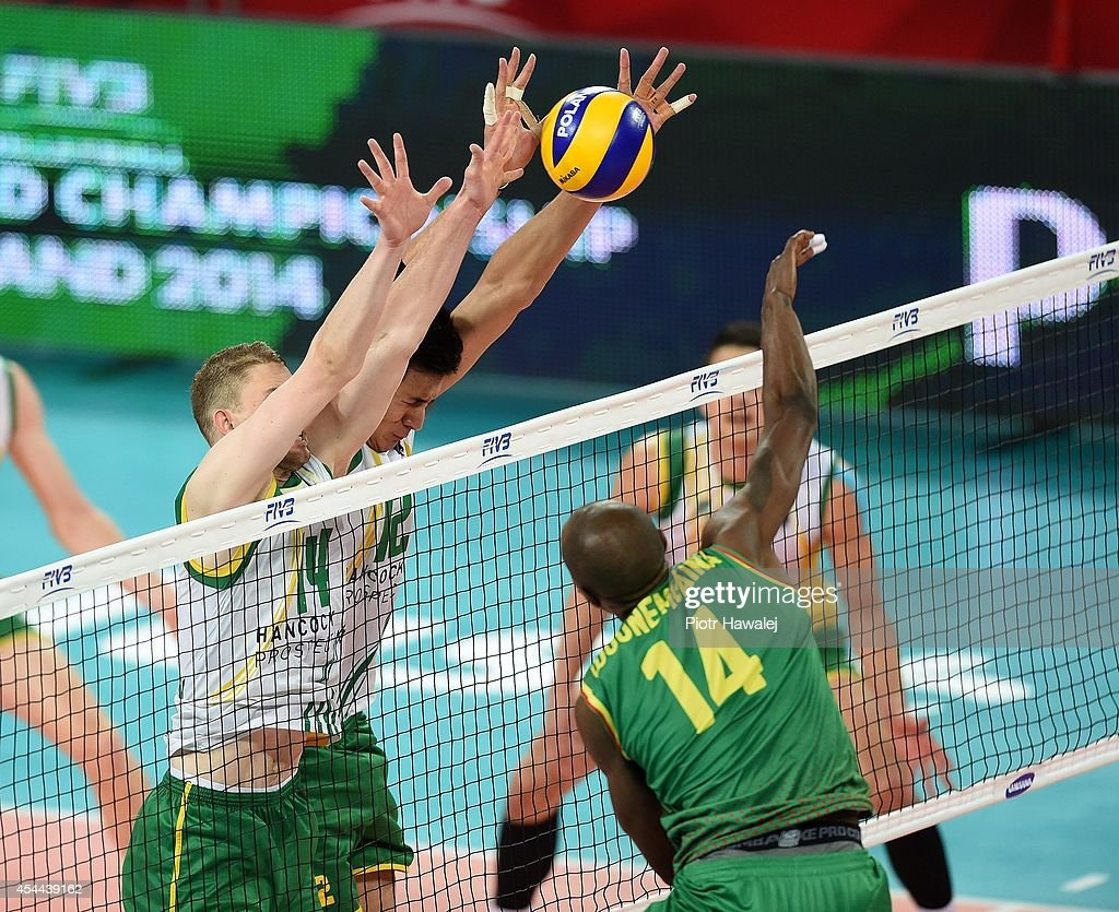 Australia players Grigory Sukochev and Nehemiah Mote defend against Cameroon's Nathan Wounembaina during the FIVB World Championships match between Cameroon and Australia on August 31, 2014 in Wroclaw, Poland.