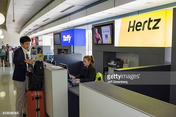 Australia Queensland Brisbane Brisbane Airport BNE terminal concourse car rental counter Hertz Thrifty competing businesses Asian man customer woman...