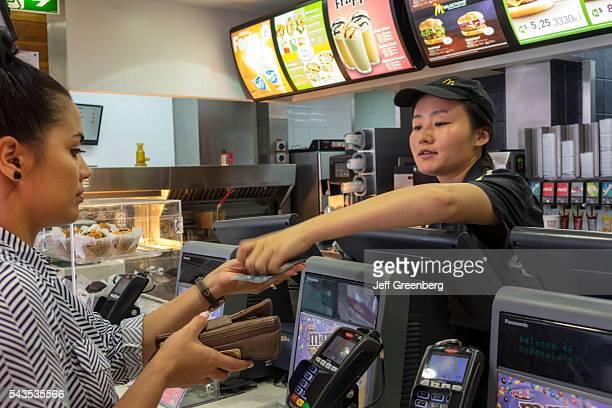 Australia Queensland Brisbane Fortitude Valley Chinatown McDonald's fast food restaurant Asian woman employee counter job service giving change...