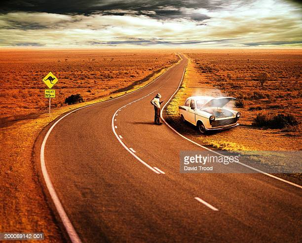 Australia, Queensland, man by broken down car on Outback road