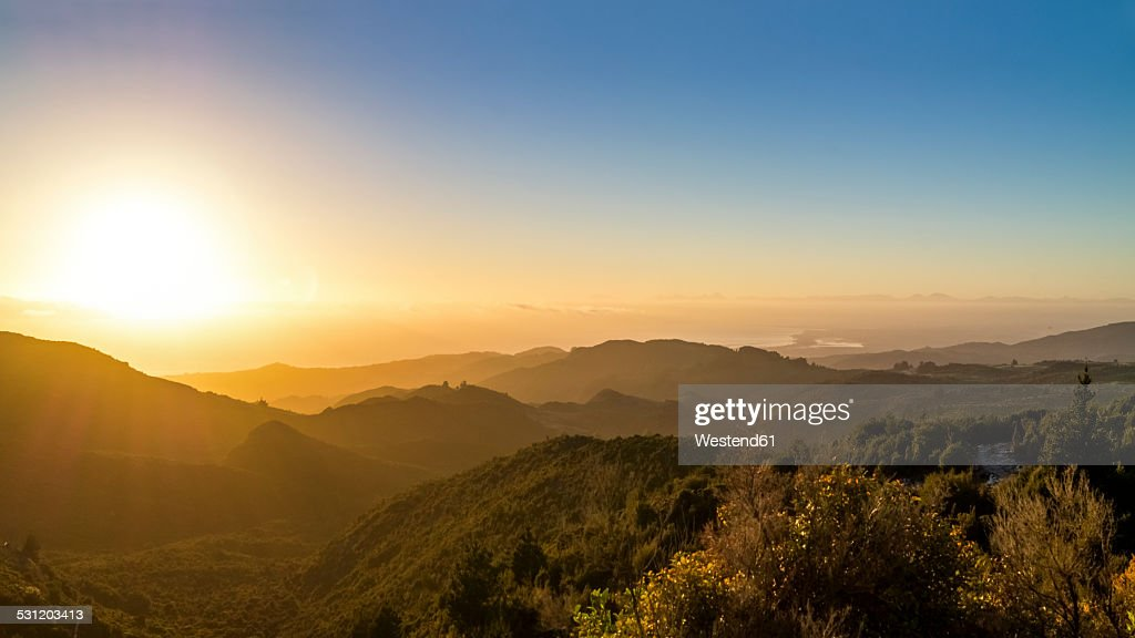 Australia, Queensland, sunrise above the ocean seen from mountains