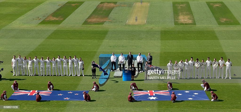 Australia (R and New Zealand (L) stand for their national anthems during day one of the first cricket international five-day Test match between New Zealand and Australia at Basin Reserve in Wellington on February 12, 2016. / AFP / Marty Melville