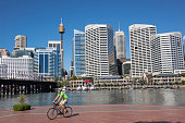 Australia Sydney Central Business District CBD Darling Harbor Cockle Bay Promenade Wharf water skyscrapers city skyline man bicycle biker biking...