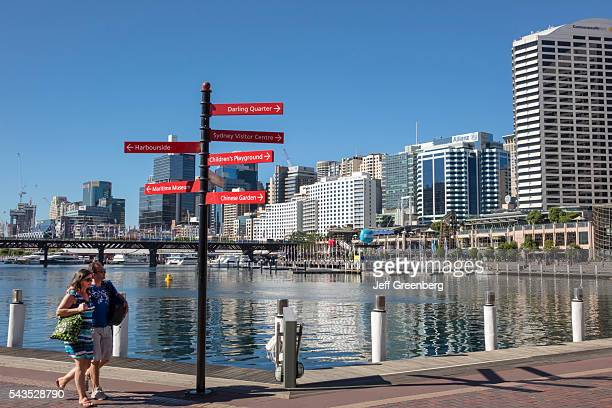 Australia Sydney Central Business District CBD Darling Harbor Cockle Bay Promenade Wharf water skyscrapers city skyline man walking woman couple sign...