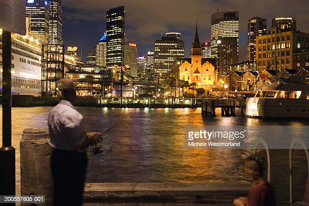 Australia, Sydney, man looking at city skyline at night, rear view