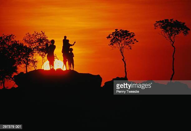 Australia,Arnhem Land,Dippirringur, silhouette of family on rock,sunse