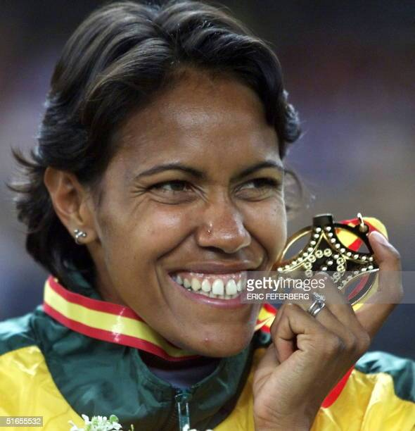 Australian 400m world champion Cathy Freeman displays her gold medal on the podium at the World Athletics Championships in Seville 27 August 1999