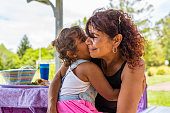 Australian Aboriginal woman giving her granddaughter a hug in the park