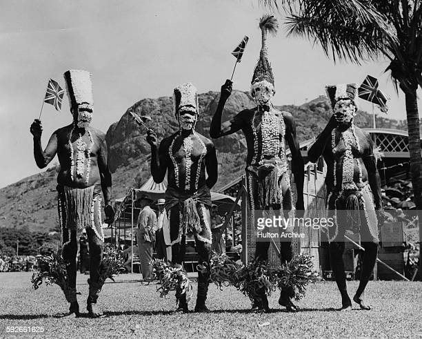Australian aborigines from Palm Island wearing traditional clothing but waving Union Jack flags welcoming Queen Elizabeth II during a visit to...