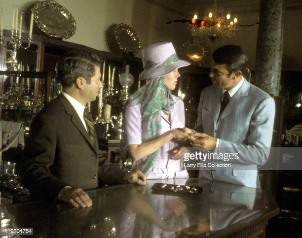 Australian actor George Lazenby and English actress Diana Rigg film a scene for the James Bond film 'On Her Majesty's Secret Service' at a jeweller's...