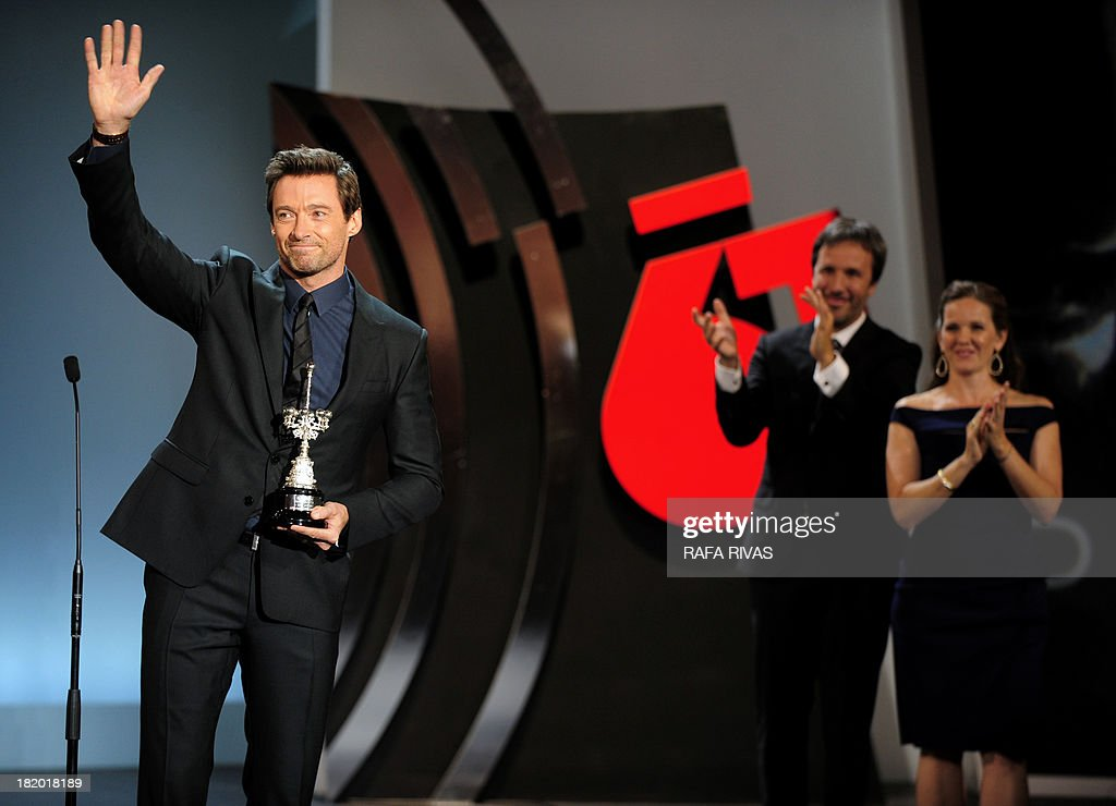 Australian actor Hugh Jackman (L) waves to the crowd after receiving the Donostia Award as Canadian director Denis Vileneuve (2nd R) and US producer Kira Davis (R) applaud during the 61st San Sebastian Film Festival in the Northern Spanish Basque city of San Sebastian on September 27, 2013.