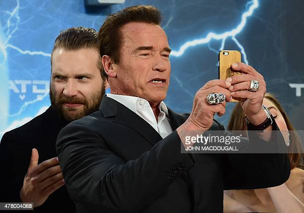 Australian actor Jai Courtney reacts on US actor and former governor of California Arnold Schwarzenegger taking a picture upon arrival for the...