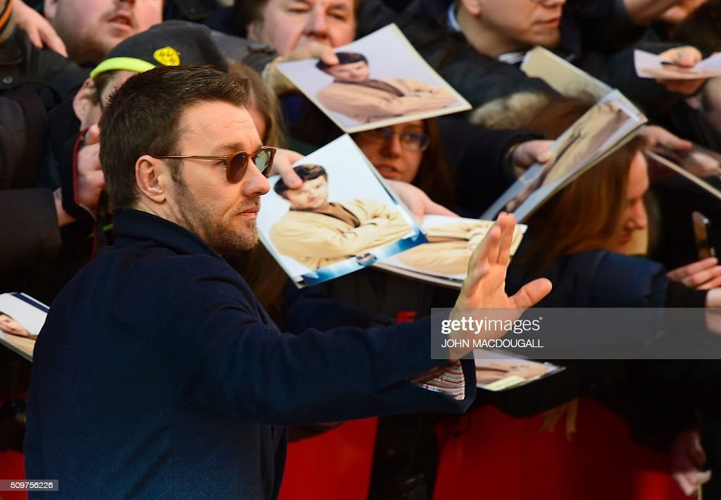 Australian actor Joel Edgerton waves as he arrives for a photo call for the film ' Midnight Special by Jeff Nichols' screened in competition of the 66th Berlinale Film Festival in Berlin on February 12, 2016. / AFP / John MACDOUGALL