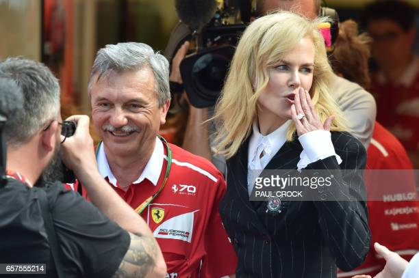 Australian actress Nicole Kidman gestures to fans as she leaves the Ferrari gargage ahead of the Formula One Australian Grand Prix in Melbourne on...