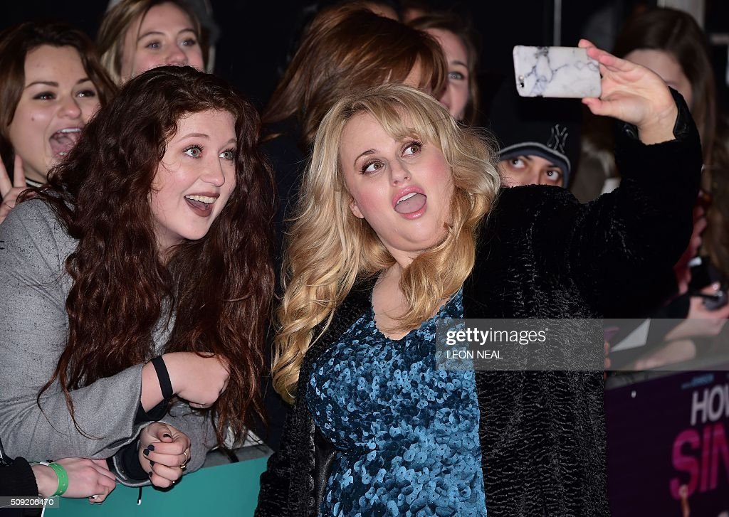 Australian actress Rebel Wilson (R) takes a selfie with a fan on the red carpet during arrivals for the European premiere of How To Be Single in London on February 9, 2016. / AFP / LEON NEAL