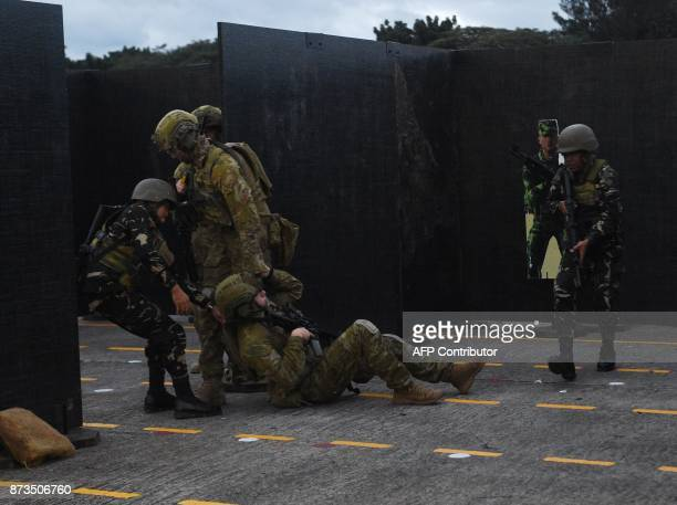 Australian and Philippine soldiers carry a wounded colleague in a simulation of antiterrorism drill during a visit by Australian Prime Minister...