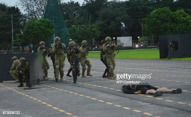 Australian and Philippine soldiers simulate and antiterrorism drill during a visit by Australian Prime Minister Malcolm Turnbull to the military...