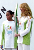 Australian athlete Cathy Freeman left and supermodel Elle MacPherson with the Queen's Baton outside Buckingham Palace London Monday March 14 2005 HM...
