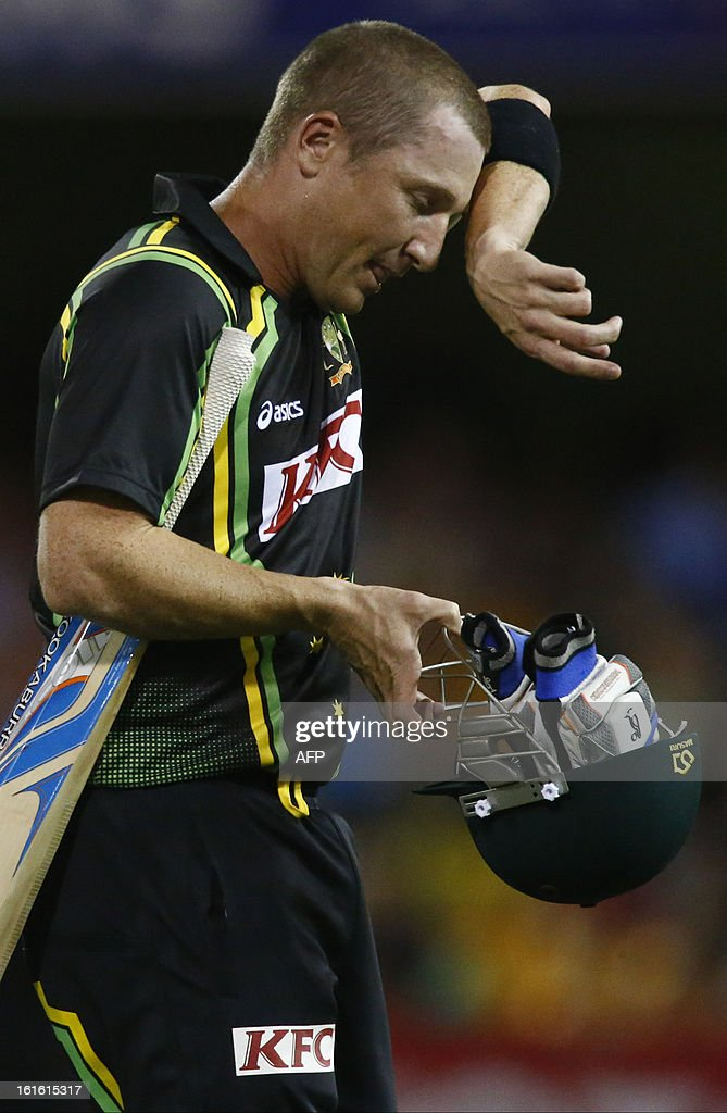 Australian batsman Brad Haddin wipes his brow after being caught by West Indian player Narsingh Deonarine during their international T20 cricket match at the Gabba cricket ground in Brisbane on February 13, 2013. AFP PHOTO / Patrick HAMILTON