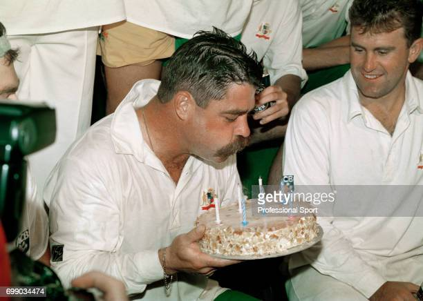 Australian batsman David Boon blows out the candles on his birthday cake watched by Australia's captain Mark Taylor after the 2nd Test match between...