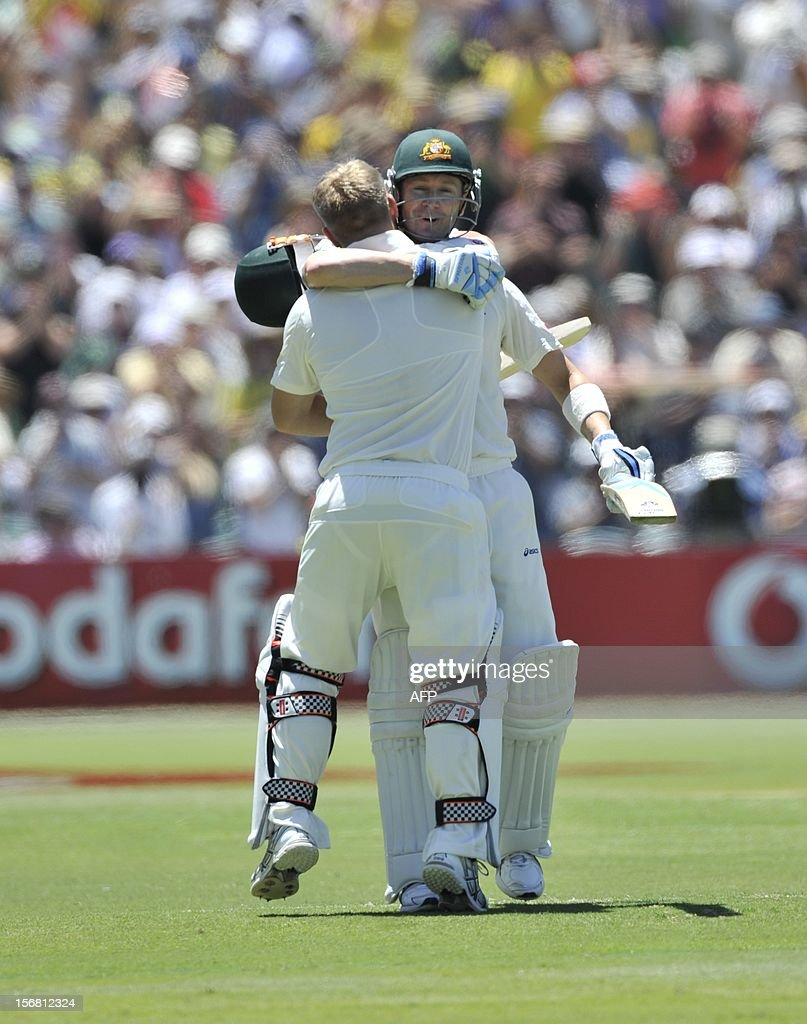 Australian batsman David Warner (L) celebrates his 100 runs with Michael Clarke batting against South Africa on the first day of the second cricket Test match at the Adelaide Oval on November 22, 2012. AFP PHOTO/David Mariuz IMAGE