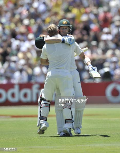 Australian batsman David Warner celebrates his 100 runs with Michael Clarke batting against South Africa on the first day of the second cricket Test...