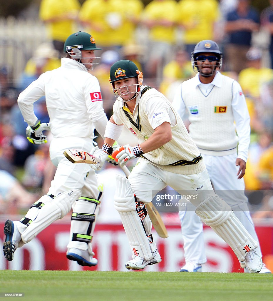 Australian batsman David Warner (C) takes off for a single with teammate Phil Hughes (L) only to be run-out as Sri Lankan Dimuth Karunaratne (R) looks on on the first day of the first cricket Test match, in Hobart on December 14, 2012. AFP PHOTO/William WEST IMAGE