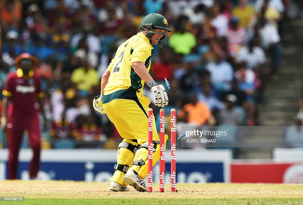 Australian batsman George Bailey is clean bowled off West Indies bowler Carlos Brathwaite during the final match of the Tri-nation Series between Australia and West Indies in Bridgetown on June 26, 2016. / AFP / Jewel SAMAD
