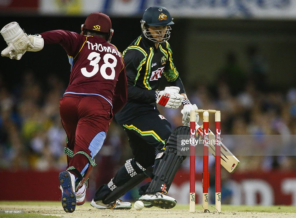 Australian batsman George Bailey protects his wicket as West Indian wick keeper Devon Thomas runs in during their international T20 cricket match at the Gabba cricket ground in Brisbane on February 13, 2013. AFP PHOTO / Patrick HAMILTON