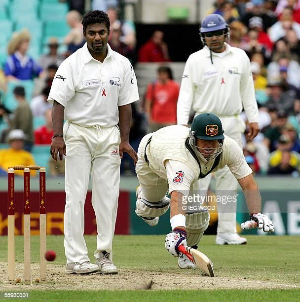 Australian batsman Matthew Hayden dives to make his ground as World XI bowler Muttiah Muralitharan and fieldsman Virender Sehwag look on during day...