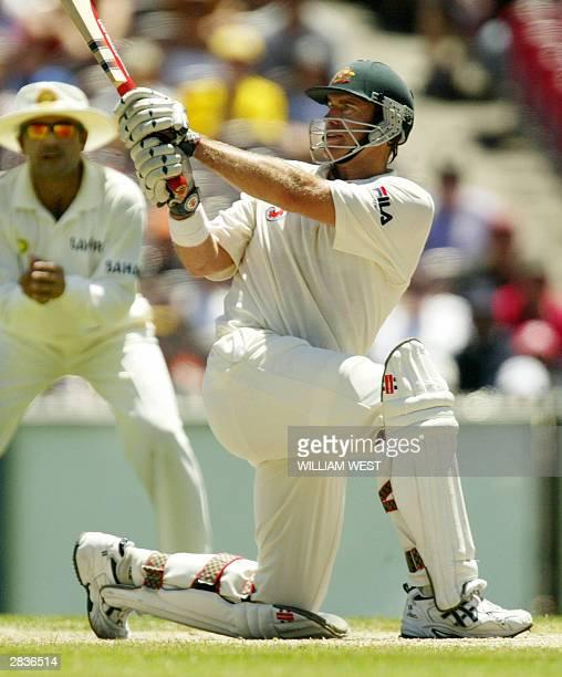 Australian batsman Matthew Hayden sweeps a ball as Indian fieldsman Virender Sehwag looks on as Australia defeats India on the final day of the third...