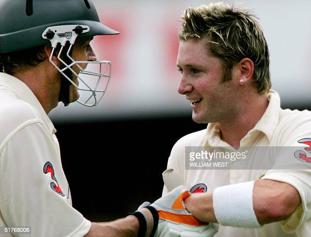 Australian batsman Michael Clark is congratulated by teammate Adam Gilchrist after scoring his century against New Zealand on the third day of the...