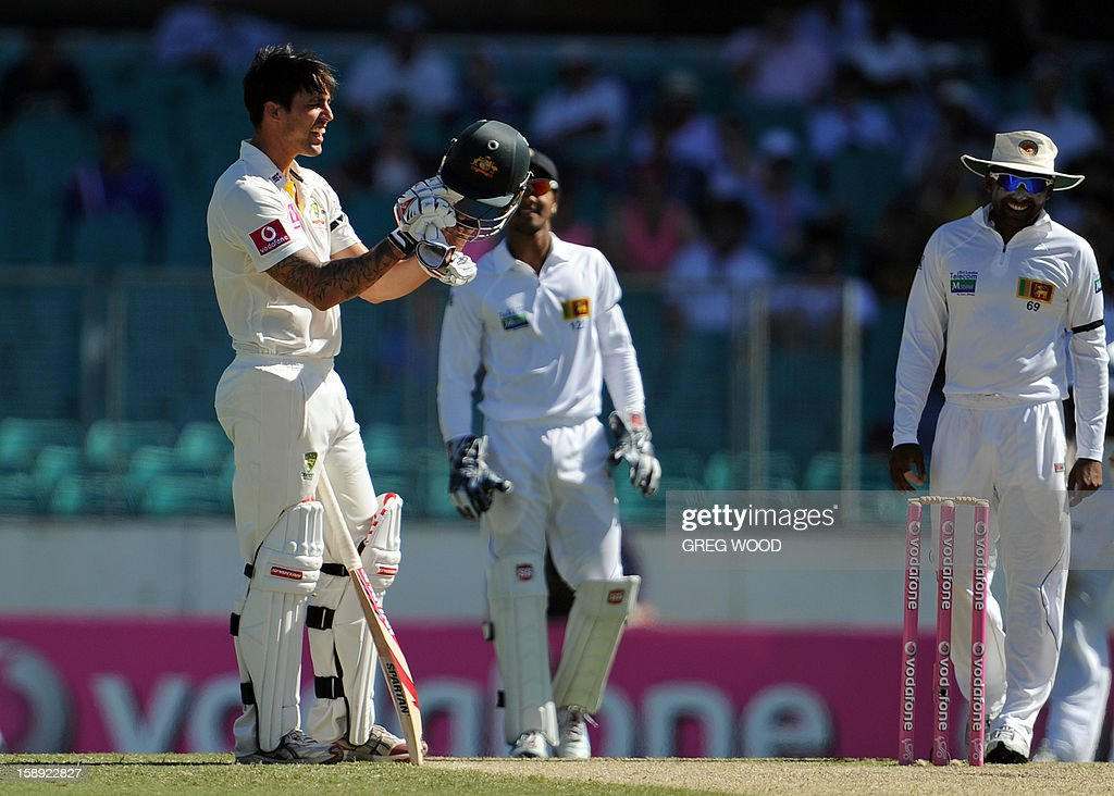 Australian batsman Mitchell Johnson (L) inspects his helmet after he was hit by the ball on day two of the third cricket Test between Sri Lanka and Australia at the Sydney Cricket Ground on January 4, 2013. IMAGE STRICTLY RESTRICTED TO EDITORIAL USE - STRICTLY NO COMMERCIAL USE AFP PHOTO / Greg WOOD