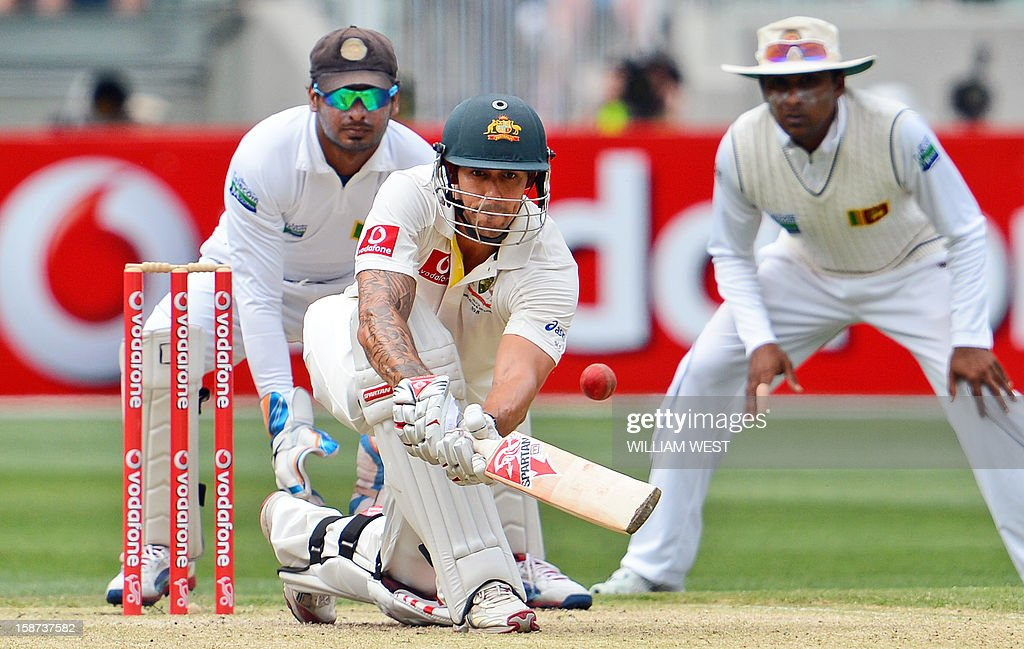 Australian batsman Mitchell Johnson (C) sweeps a delivery from the Sri Lankan bowling as wicketkeeper Kumar Sangakkara (L) and Mahela Jayawardene (R) look on on the second day of the second cricket Test match at the Melbourne Cricket Ground (MCG) on December 27, 2012. AFP PHOTO/William WEST IMAGE
