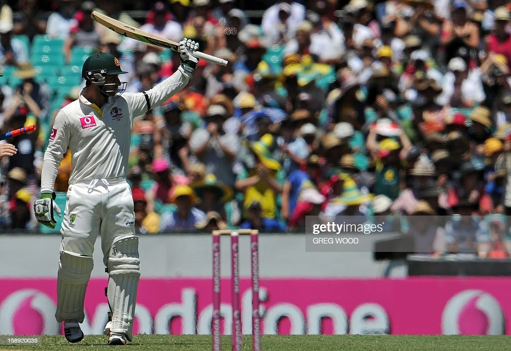 Australian batsman Phil Hughes (L) raises his bat after reaching his 50 on day two of the third cricket Test between Sri Lanka and Australia at the Sydney Cricket Ground on January 4, 2013. IMAGE STRICTLY RESTRICTED TO EDITORIAL USE - STRICTLY NO COMMERCIAL USE AFP PHOTO / Greg WOOD
