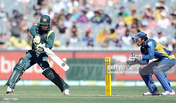 Australian batsman Phillip Hughes plays a shot on his way to a century as Sri Lankan wicketkeeper Dinesh Chandimal looks on during the first oneday...