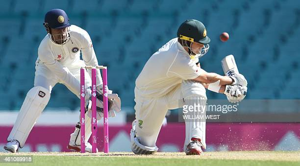 Australian batsman Shane Watson sweeps a delivery in front of Indian wicketkeeper Wriddhiman Saha on the first day of the fourth cricket Test at the...