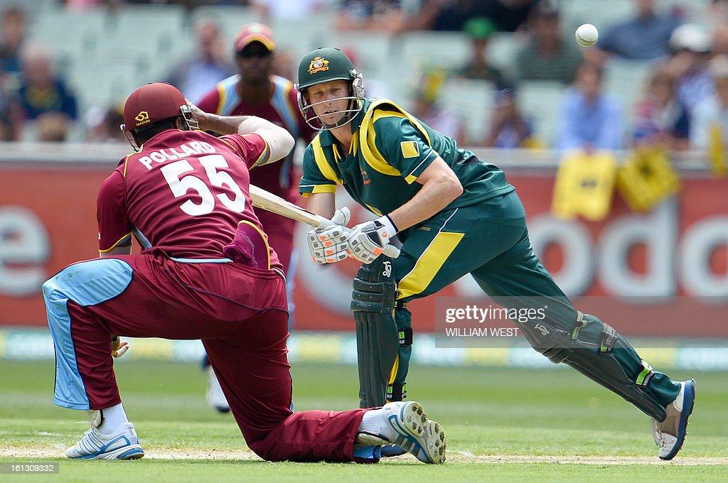 Australian batsmen Adam Voges (R) steers a ball past West Indies fielder Kieron Pollard (L) in their one-day cricket international played at the Melbourne Cricket Ground (MCG), on February 10, 2013. AFP PHOTO/William WEST IMAGE