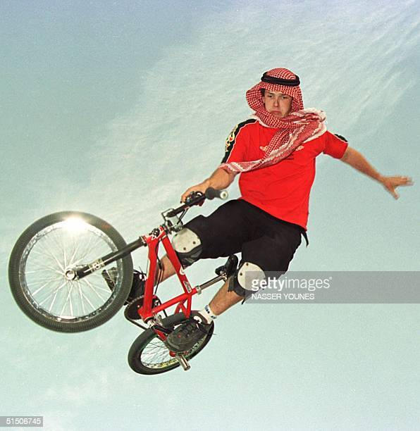 Australian biker Dinny Spicer wearing a traditional Arab head scarf performs on his BMx freestyle in Kuwait 11 February 2001 Spicer belongs to the...