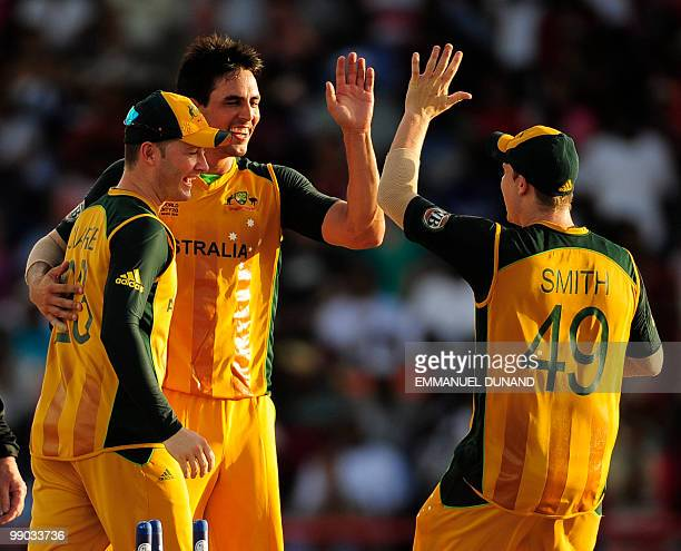 Australian bowler Mitchell Johnson celebrates with captain Michael Clarke and Steven Smith after taking the wicket of West Indies batsman Dwayne...