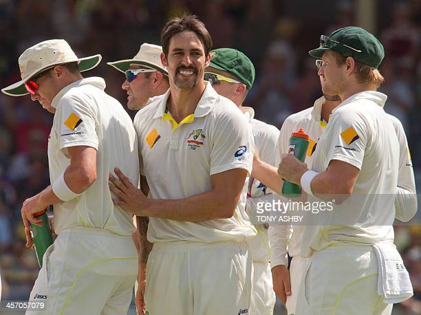 Australian bowler Mitchell Johnson celebrates with teammates after dismissing England batsman Joe Root on the fourth day of the third Ashes cricket...