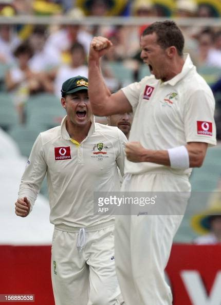Australian bowler Peter Siddle and Michael Clarke celebrate the dismissal of South African batsman Abraham de Villiers on the third day of the second...